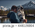 Man playing with his dog outdoors mountain terrain 44619864