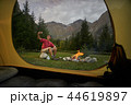 View from inside tourist tent. Alone tourist, man hiker sitting at bonfire, selfie by cellphone 44619897