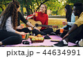 Young men and women are toasting and clinking glasses on picnic in park with guitar on warm autumn 44634991