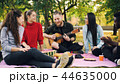 Joyful hipster is singing and playing the guitar sitting on blanket in park with friends and having 44635000