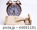 ベッドで寝る人形と脇に置いた目覚まし時計 44691191