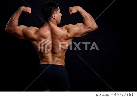 bodybuilder with raised arms posing to the camera 44727361