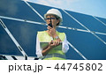 An engineer works with devices, standing on a roof near solar batteries. Alternative, green energy 44745802