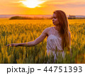 Girl touch ears of wheat at sunset 44751393