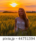 Pretty girl in field at sunset 44751394