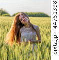 Pretty girl in field at sunset 44751398
