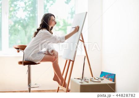 Pretty female artist painting artwork at studio 44828782