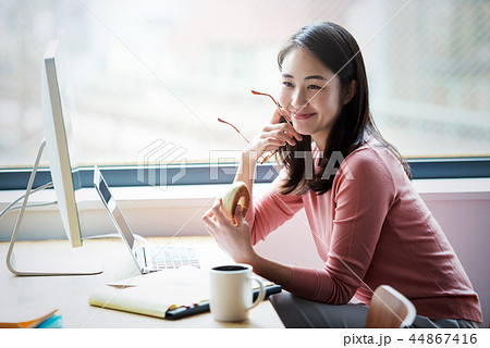 オフィスの女性、軽食をとりながらの仕事。 44867416