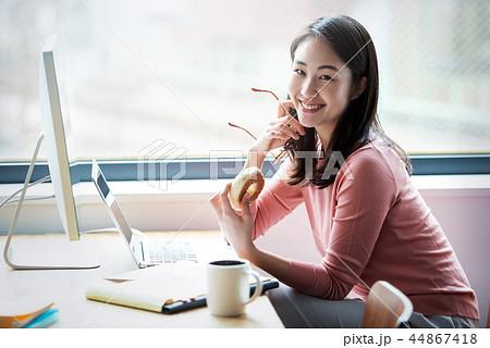 オフィスの女性、軽食をとりながらの仕事。 44867418