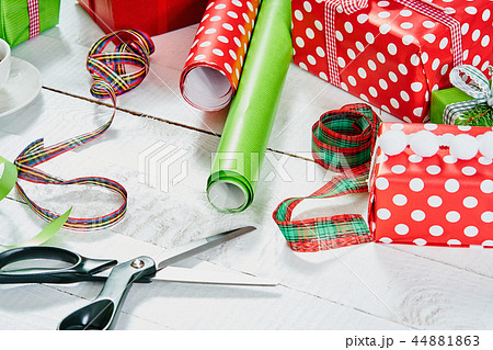 colorful papers for wrapping Christmas gifts and scissors on a white wooden table 44881863