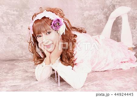 ロリータ ピンク 全身 寝そべって両手で頬杖して微笑む女性 44924445