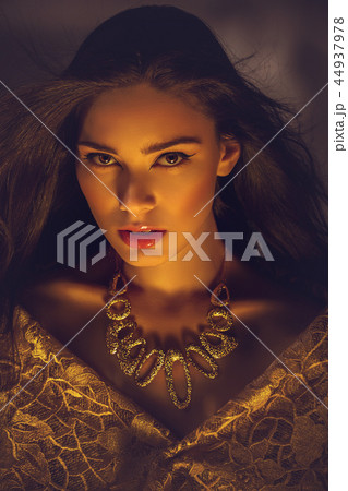 beautiful young woman with necklace in golden light 44937978
