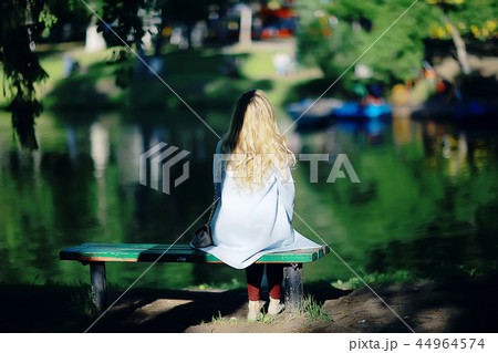adult girl sitting on a bench in the park / beautiful model woman resting on a bench, cheerful happy girl 44964574