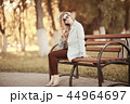 adult girl sitting on a bench in the park / beautiful model woman resting on a bench, cheerful happy girl 44964697
