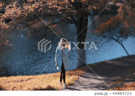 walk in autumn park / beautiful girl in autumn park, model female happiness and fun in yellow trees October 44964723