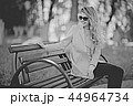 adult girl sitting on a bench in the park / beautiful model woman resting on a bench, cheerful happy girl 44964734