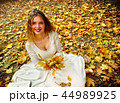 Autumn fashion dress woman sitting fall leaves city park outdoor. 44989925