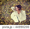 Autumn fashion dress woman sitting fall leaves city park outdoor. 44990200