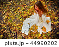 Autumn fashion dress woman sitting fall leaves city park outdoor. 44990202