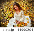 Autumn fashion dress woman sitting fall leaves city park outdoor. 44990204