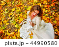 Autumn fashion dress woman sitting fall leaves city park outdoor. 44990580