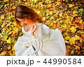 Autumn fashion dress woman sitting fall leaves city park outdoor. 44990584