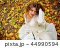 Autumn fashion dress woman sitting fall leaves city park outdoor. 44990594