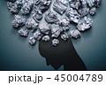 うつや不安のイメージ。紙くずとうつむいた人の頭のシルエット。 45004789