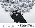 メンタルヘルスのイメージ。紙くずとうつむいた人のシルエット。 45004791