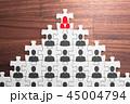 女性リーダーと組織のピラミッド構造。人事とリーダーシップ。木の机でパズルを組む。 45004794