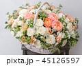 Wicker basket with mix beautiful flowers on wooden table near gray wall. Beautiful garden flowers in 45126597