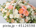 Wicker basket with mix beautiful flowers on wooden table near gray wall. Beautiful garden flowers in 45126598