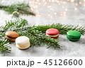 Merry Christmas card. Variety of sweet macaroons and fir branches on a gray vintage background. flat 45126600