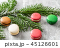 Merry Christmas card. Variety of sweet macaroons and fir branches on a gray vintage background. flat 45126601