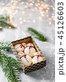Variety of sweet macaroons in carton box. Cookie in the form of a snowman. Fir branches on a gray 45126603