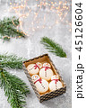 Variety of sweet macaroons in carton box. Cookie in the form of a snowman. Fir branches on a gray 45126604