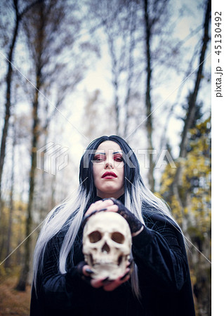 Image of witch woman with skull in hands 45130492