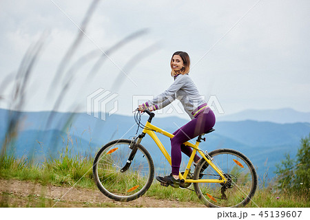 Young Happy Woman Cycling On Mountain Bike At Summer Dayの