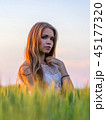 Pretty girl in field at sunset 45177320