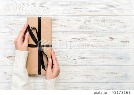 Woman hands give wrapped  present in paper  45178168