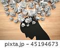 ストレスやメンタルヘルスのイメージ。紙くずとうつむいた人の頭のシルエット。木の板の背景。 45194673