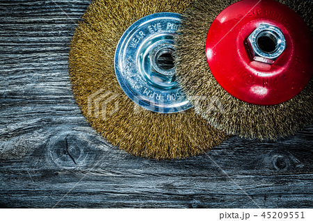 Brass wheel brushes on vintage wooden board 45209551