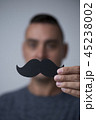 young man with a fake moustache. 45238002