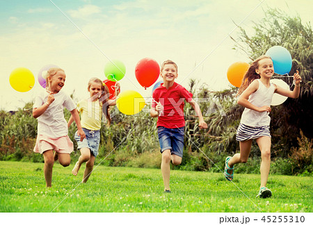children running with air balloons in park . 45255310