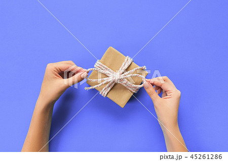 Woman hands give present in paper with pink ribbon 45261286