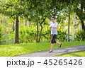Young woman jogging in a park looking to smart way 45265426