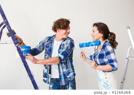 Repair, renovation and love couple concept - Young woman and man doing repair with happy faces 45266368