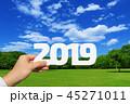 2019年を持つ男性の手と青空と新緑の草原背景 45271011