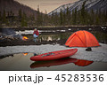 View of camp life in a mountain terrain. Lake shore with canoe 45283536