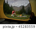 View from inside tourist tent. Man hiker sitting at bonfire, making selfie photo by mobile phone 45283559